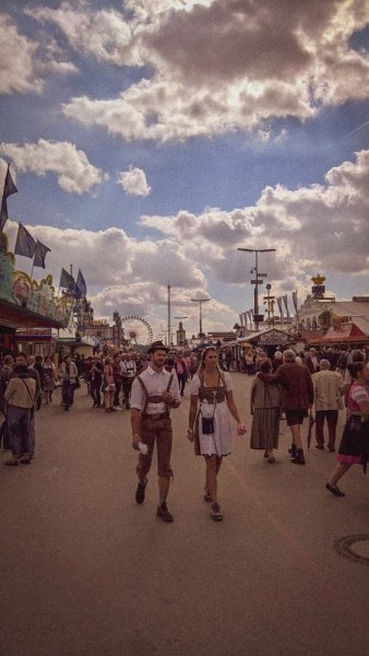A young man and a woman walking on the Oktoberfest grounds in traditional German clothing.