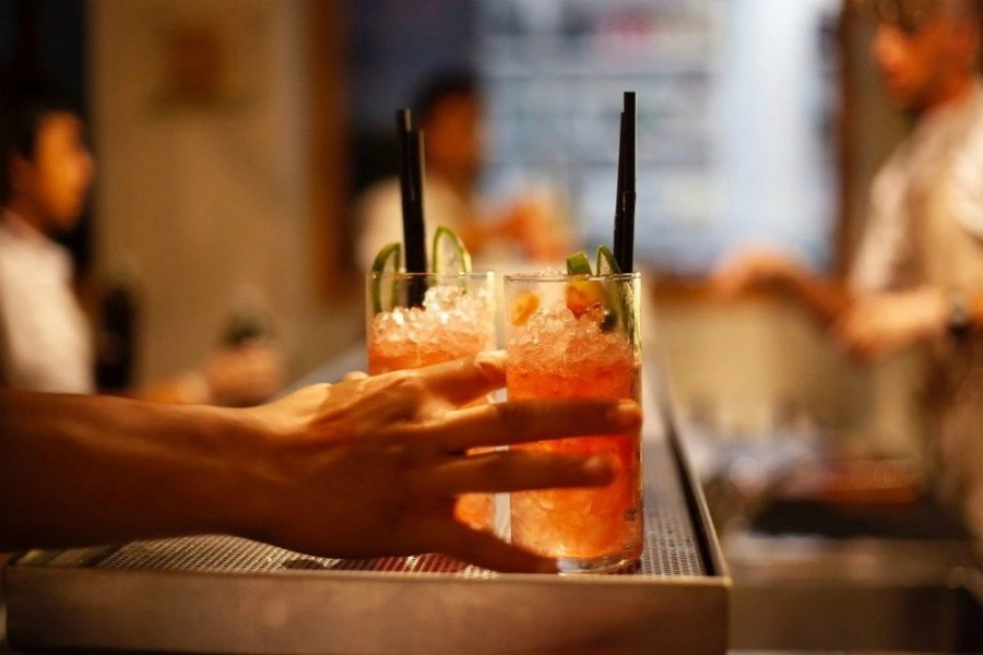 A hand grabbing two tall cocktail drinks from the bar.