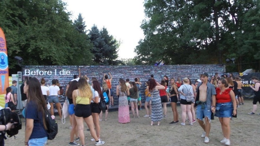 "A long wall with written desires and bucket lists of ""Before I die"" at Sziget Festival."