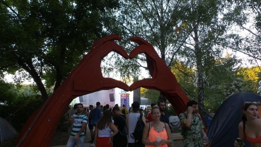Sculpture of two red hands making a heart sign above a crowd of people at a festival.