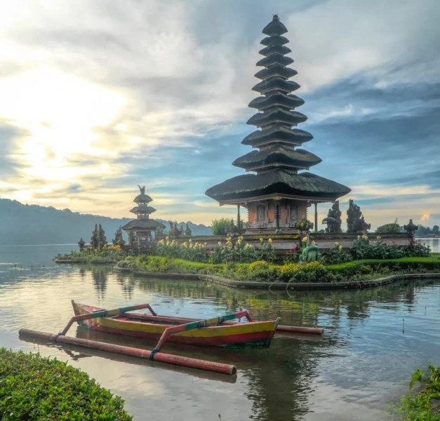 Ancient temple on an island around a body of water in Bali, Indonesia.