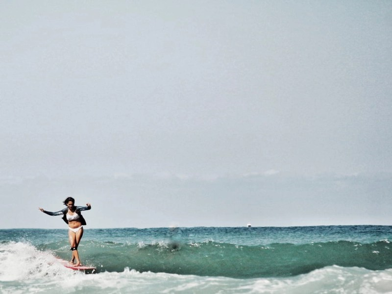 A woman in a bathing suit surfing on a surfboard in a body of water.