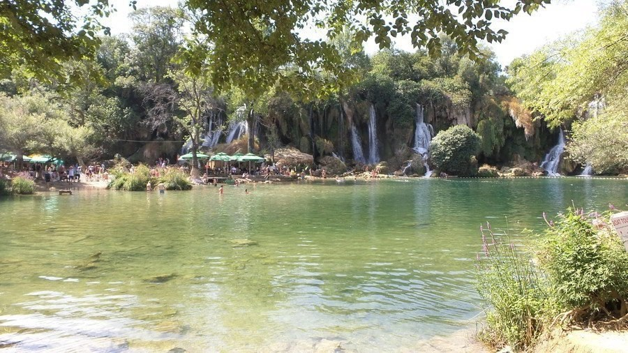 Crowd of people around a water of body and waterfalls.