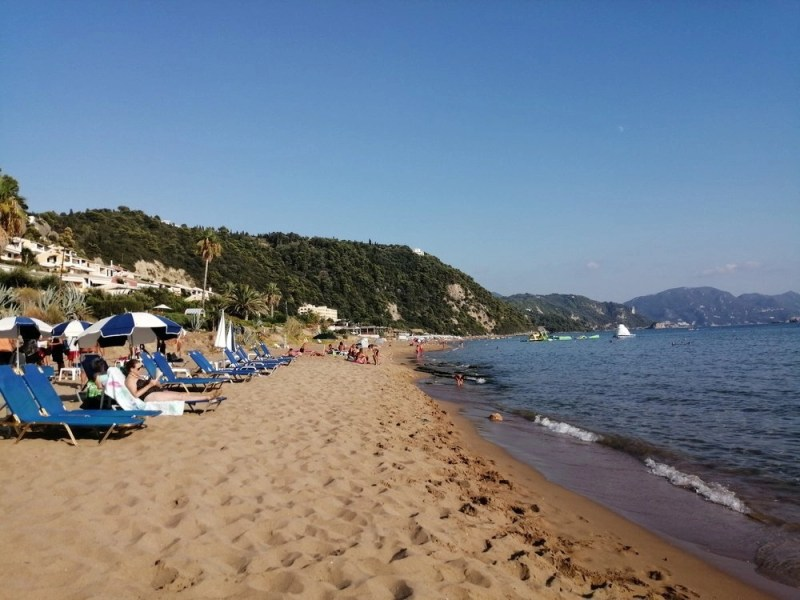 People laying on sunbeds on a beach near sea.