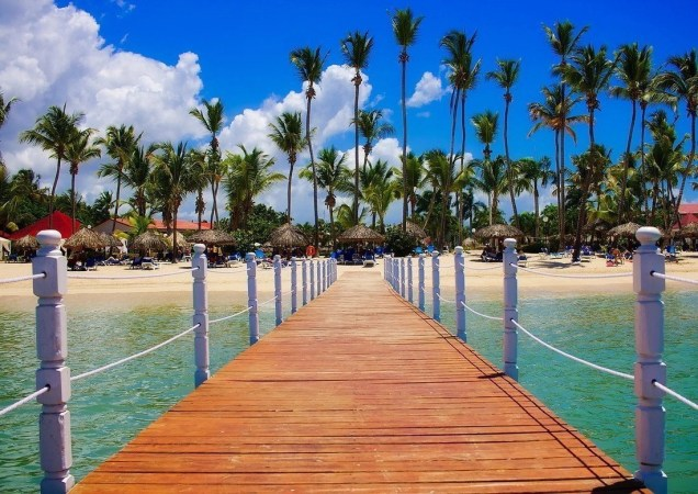 Wooden pier in a body of water leading to the shorelines of a beach.