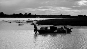pescatore trascina barca al tramonto, bianco e nero