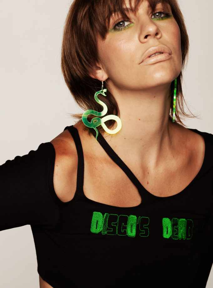 black sweater with cut outs and neon yellow snake earrings