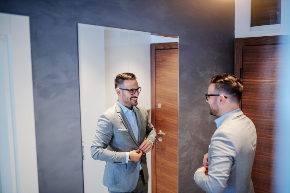 Man in suit practicing interview skills in front of the mirror