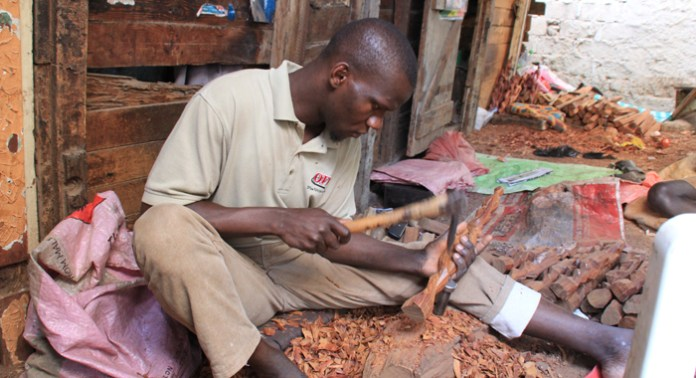 A man carves wooden art outside a craftshop in a slum area of Dakar. (IWN photo)