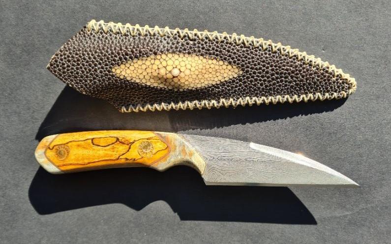 Damascus jachtmes. Houtsnijwerk van Afrikaans teak, bolsters van mammoet ivoor, inleg van ammoniet fossiel. Schede is gemaakt van roggenleer