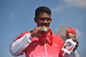 Atlet dayung putra Indonesia Marjuki menggigit medali emas ketika prosesi penyerahan medali setelah finish pertama final kano nomor C1 1000 meter putra SEA Games ke-28 di Teluk Marina, Singapura, Sabtu (6/6). Marjuki mempersembahkan medali emas pertama bagi Indonesia. ANTARA FOTO/Wahyu Putro A/Rei/nz/15.