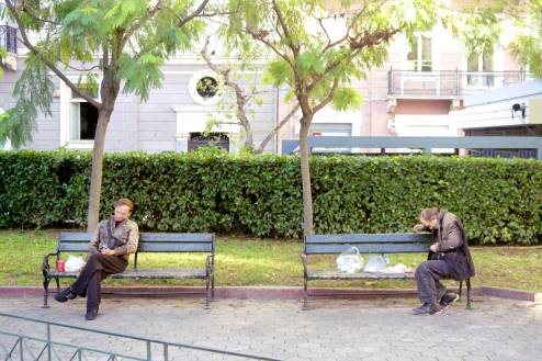Men sitting on opposite sides of two benches.