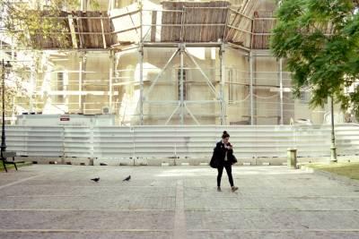 A woman walking alone through a square