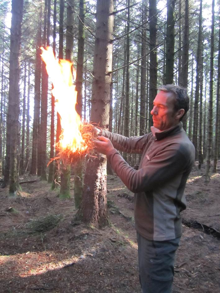 Gary using an ember from a spruce fire by friction set