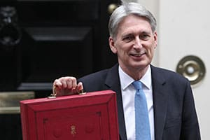 LONDON - 22ND, NIV 2017: Chancellor of the Exchequer, Philip Hammond, holds the famous red box on the steps of Number 11 Downing street, before leaving for the Palace of Westminster to deliver it to the House