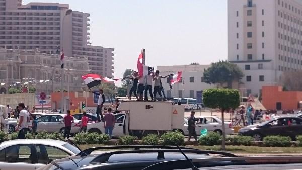 Revelers atop a van in Tahrir Square.