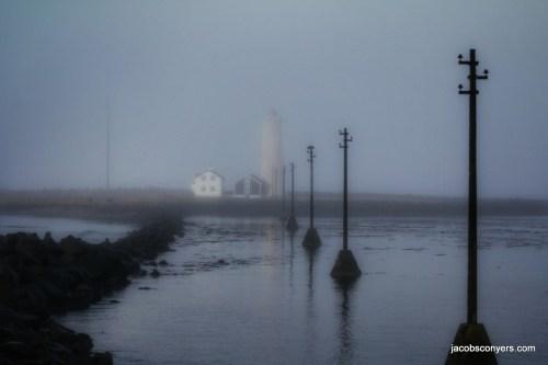 A lighthouse barely peeking through the fog