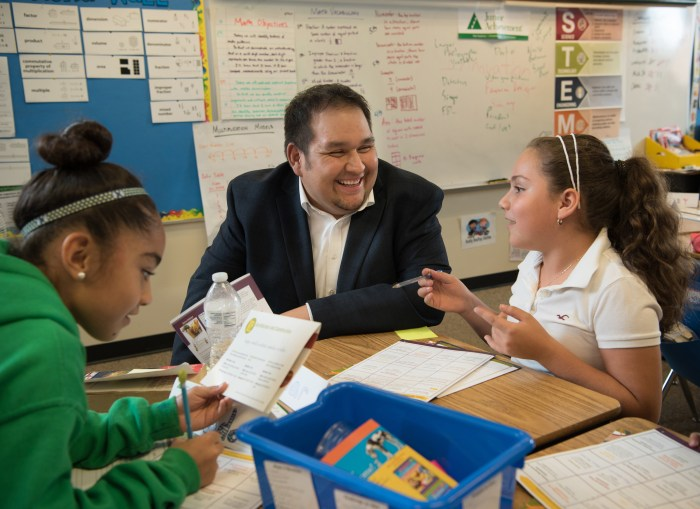 A volunteer works with two children in a Junior Achievement classroom