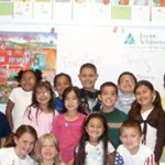Adult volunteers posed in classroom with elementary school students