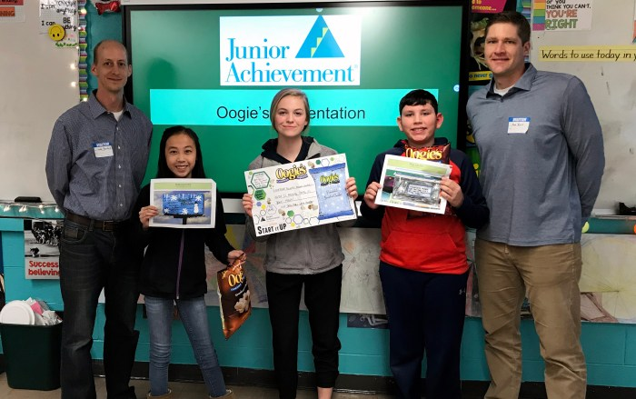 Three middle school students holding up Junior Achievement materials with two adult volunteers