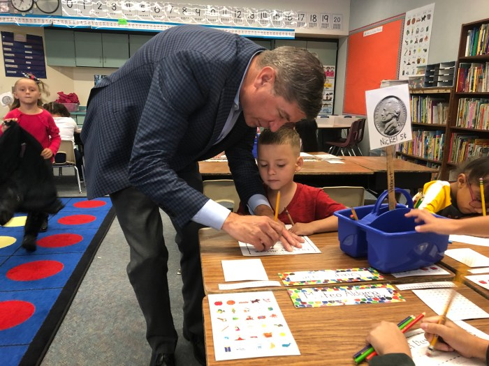Chris Gdowski assists a student in classroom