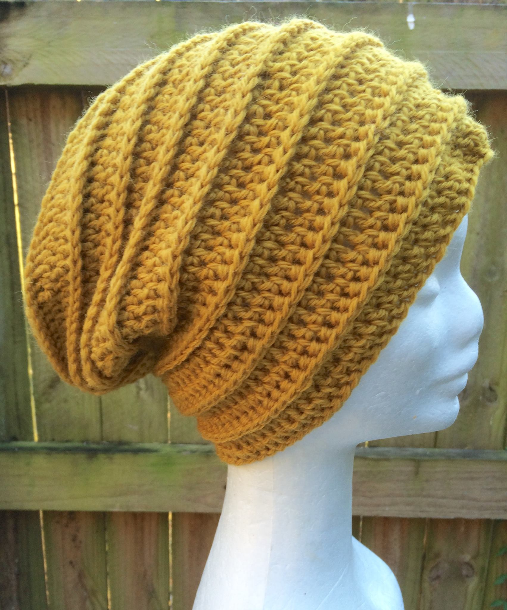 9e2a70cc2 Crocheted Slouchy beanie in mustard yellow with a textured ribbed effect.