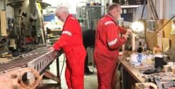 Statistene Stein og Roar skulle drive med restaureringsarbeider på He 115 i bakgrunnen mens filmingen pågikk.