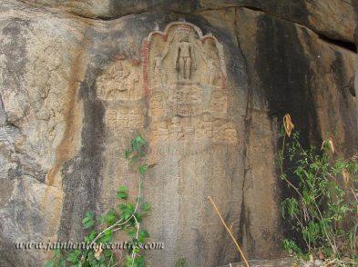 Carvinfs of a Tirthankar and inscription on a rock.