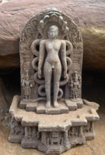 A highly embellished sculpture of Parsvanatha of the Hoysala period under the canopy formed by the hood of a snake is shown standing on a simha throne flanked by a yaksha and yakshi. Photo:K. BHAGYA PRAKASH