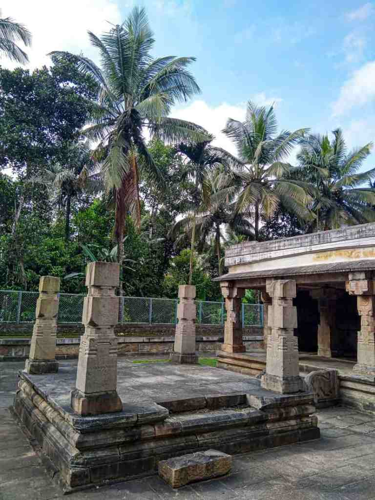 The remnants of the detached mandapa, with Wayanad's swaying palm trees in the background.