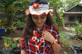 Matching hat, ring & necklace made from red & white plastic bags.