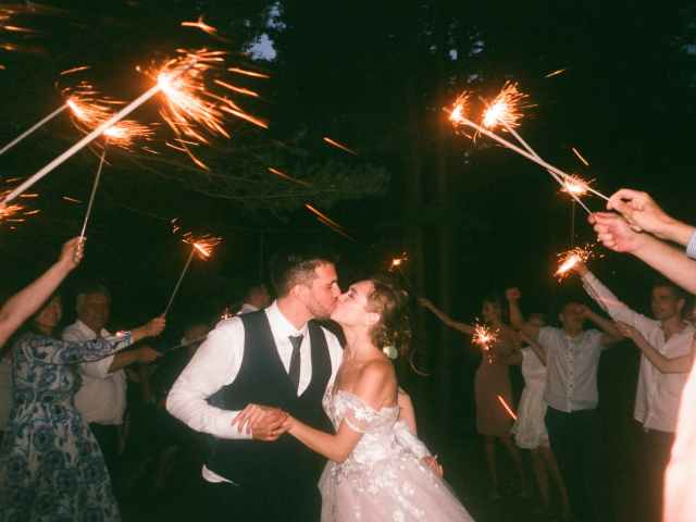 people raising lit sparklers while encircling bride and groom kissing