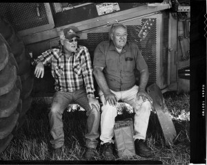 Two workers taking a break after performing maintenance on their combines during the 2015 Oklahoma wheat harvest.