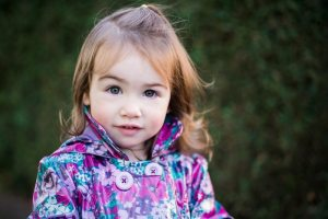 Toddler standing in front of a green background
