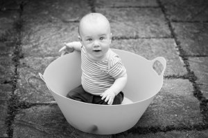 Baby boy playing in a clothes basket
