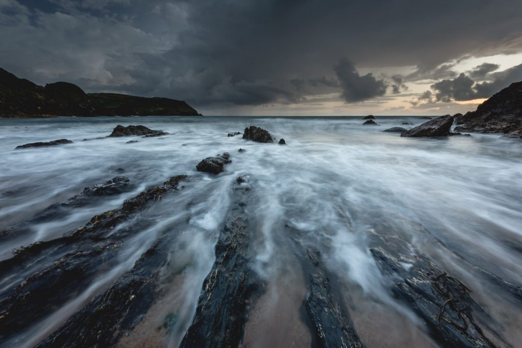 A long exposure of a moody and dramatic sunset at Hope Cove in South Devon
