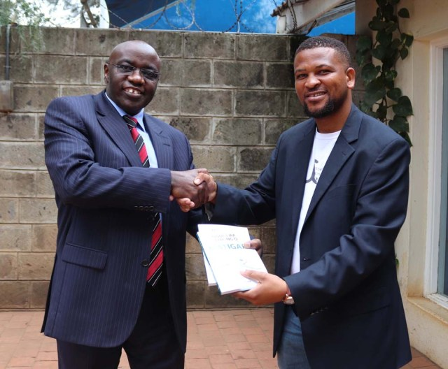 East African Educational Publishers boss Kamau Kiarie receives the new book from Ethale Publishing's Jessemusse Cacinda