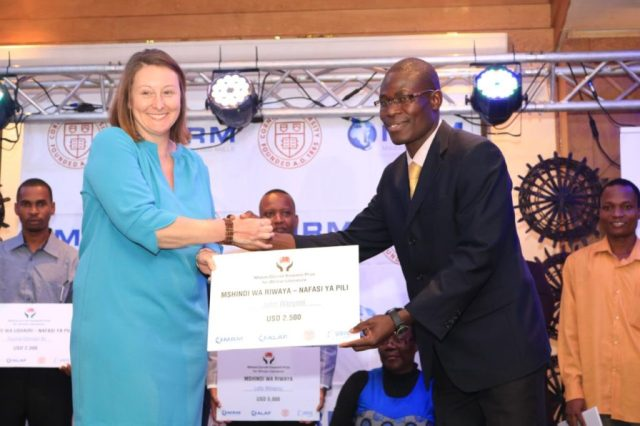 Dr Lizzy Attree hands second prize winner John Wanyonyi his award