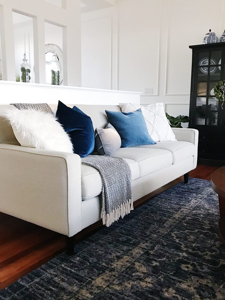 Make Your Home Feel More Cozy - blue and white living room with blue vintage rug, velvet pillows and panel molding