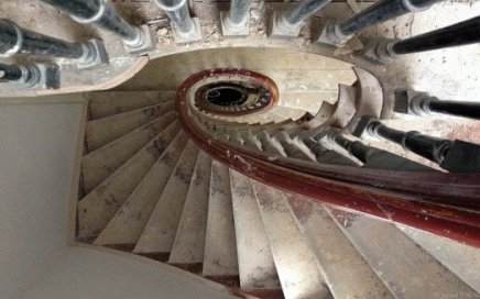 a top-down view of a spiral staircase with red bannister