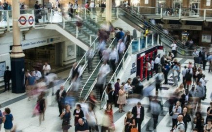 A time-lapse photo of peopl milling about an interior with stairs and an escalator.