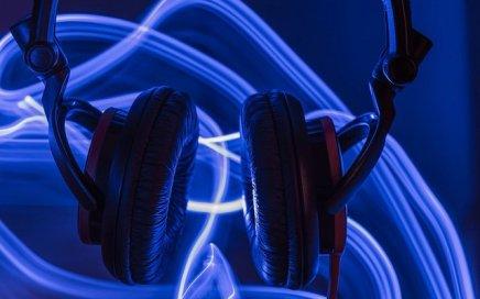 Headphones in front of purple luminescent waves