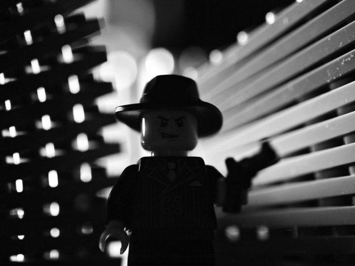 Image: Lego man holding gun in film noir lighting