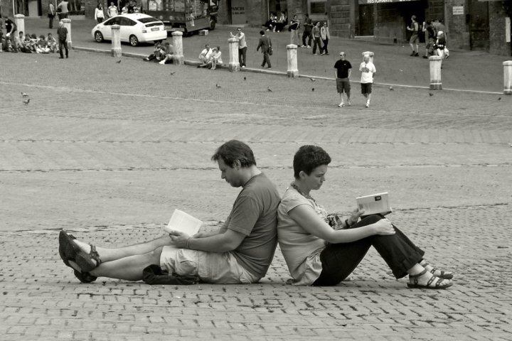 Image: book readers sitting back-to-back on the ground