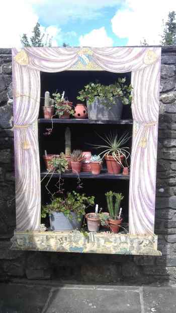 Cabinet of succulent plants framed with wood 'curtains' like a theatre