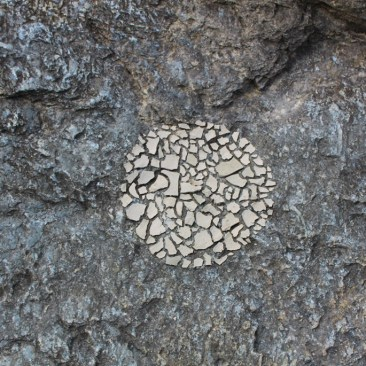 Land Art: Dried mud packed in a circle on river-side rock