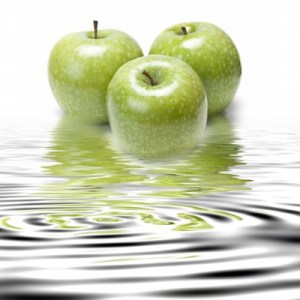 3 green apples sitting in clear water