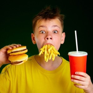 a young boy eating a fast food hamburger, french fries and a cola