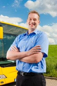 a busdriver standing by his bus smiling with his arms crossed