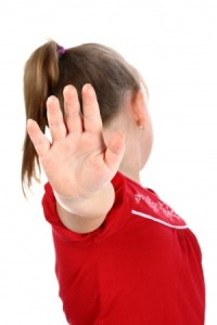 A young girl in a red dress holding her hand up saying no.